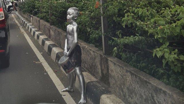 Pria dengan tubuh dicat dengan warna silver