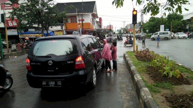 Pengemis beraksi meminta sedekah kepada pengguna jalan di salah satu lampu merah di Makassar, Sabtu (10/4/2021).