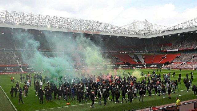 Suporter memasuiki lapangan Stadion Old Trafford membuat laga MU vs Liverpool terancam ditunda, Minggu (2/5/2021). Foto: NSport Thenationalnews.com