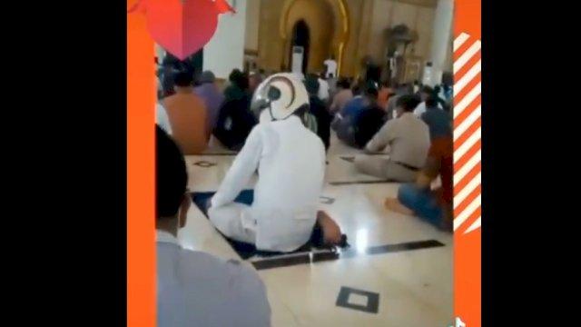 Tangkapan layar video viral pria salat pakai helm.