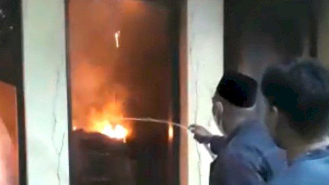 Warga yang berusaha memadamkan api dengan alat seadanya di rumah dinas Kapolres Parepare.